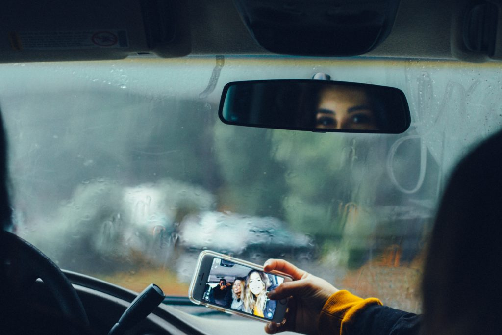woman's reflection in rear view mirror with phone revealing a group picture. Photo by Omar Lopez on Unsplash