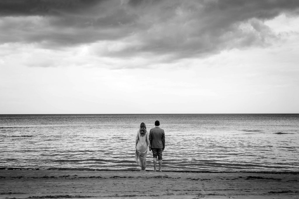 Woman and man standing next to each other and looking out at the ocean